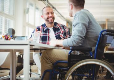 Two students in conversation, one is in a wheelchair