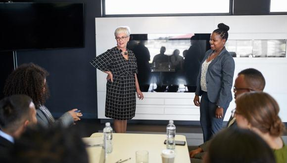 two women presenting in a boardroom